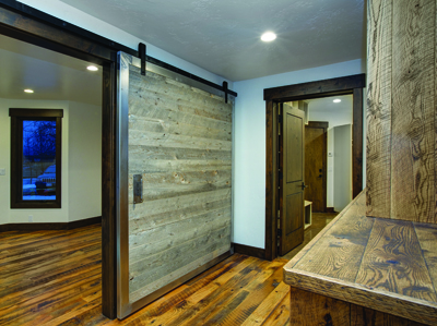 Steel framed barn door built of Nature Aged Wood in a steel frame. Floor is Reclaimed Oak, both by Todd Arenson Construction